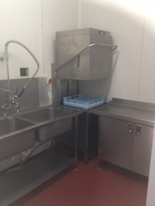 Pass through dishwasher with inlet sink and outlet table